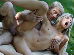 A young blonde babe is getting scored by an very old fellow outdoors